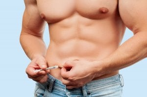 A man giving himself a shot in the abdomen.