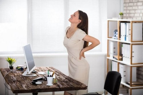 A woman suffering from back pain due to a poor posture when sitting down at work