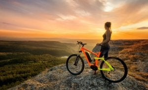 A woman on a hill with her bike.