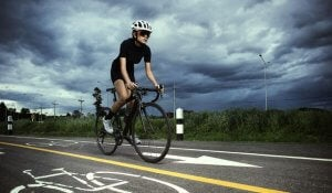 A woman riding a bike in stormy weather.