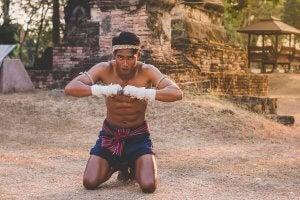 A kneeling Muay Thai fighter.