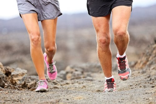 The legs of a couple jogging in the dirt.