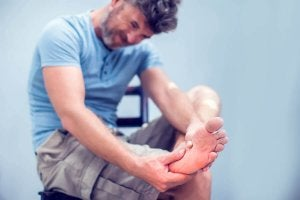 A man massaging a painful cramp in his foot.
