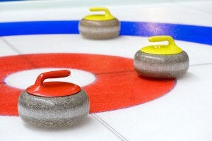 Three curling stones on the ice.