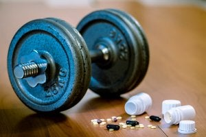 A dumbbell with bottles of pills.