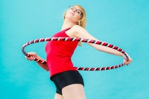 A woman about to start using a hula hoop.