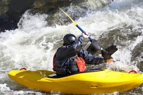 Man in a yellow kayak in the rapids to sport description in text for canoeing.