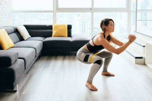Woman doing squats in front of her tv to counteract the negative impact of sitting down at work