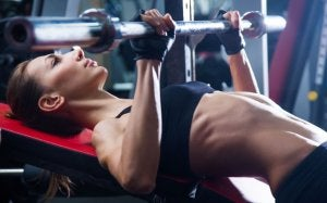 A woman lifting weights in a gym.