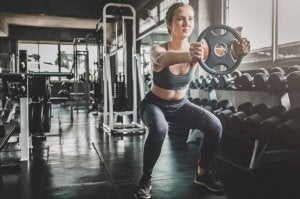 A woman doing squats with a weight in the gym.
