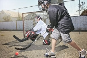 Two children playing street hockey.