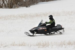 A motor sledder races across the snow.
