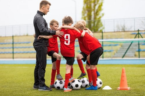 A coach encouraging teamwork in his soccer players.