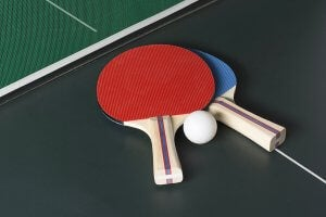 Two table tennis paddles and a ball.