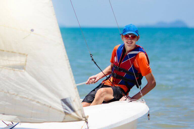 A young boy steering a sailboat durign a regatta