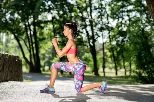 A woman doing a lunge outside.