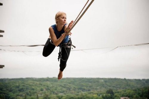 A woman with a harness doing slackline.
