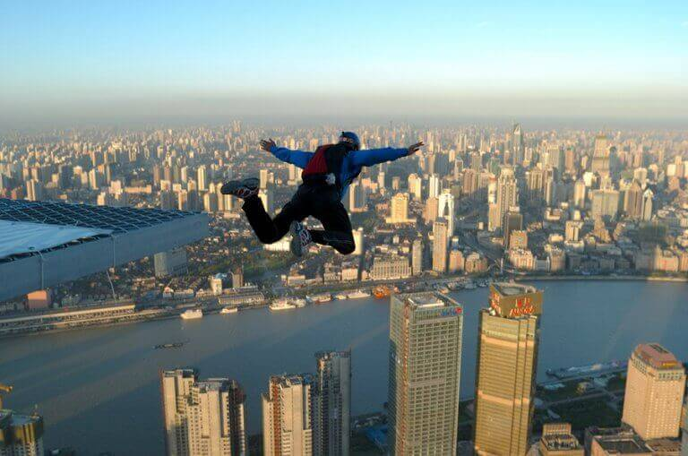 A man base jumping from a building