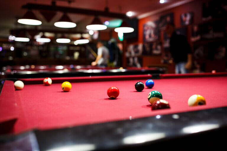 A billiards table with people playing in the background