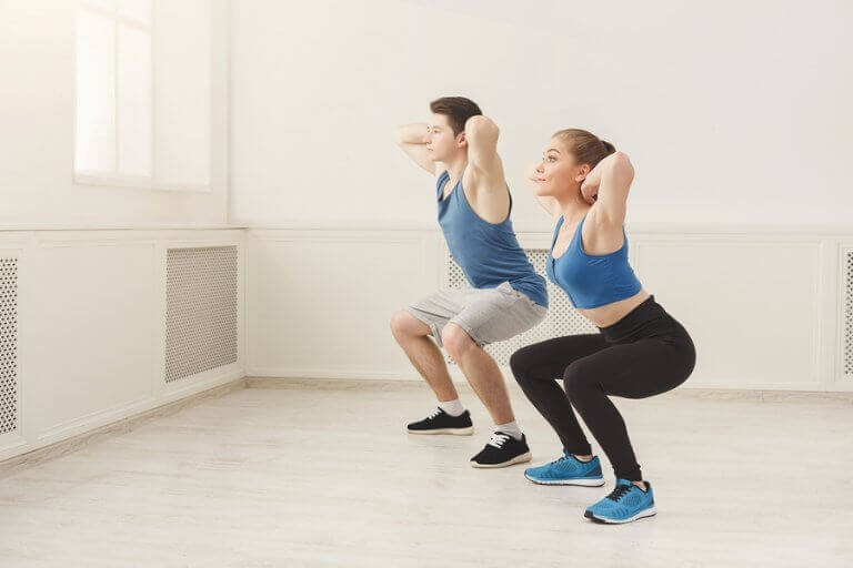 A man and a woman doing squats inside their home
