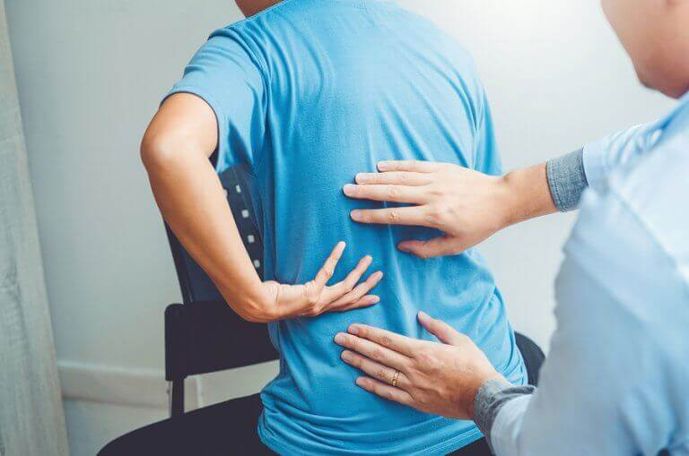 A doctor checking the back of a patient to detect herniated disks