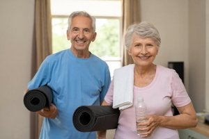 An older couple with yoga mats.