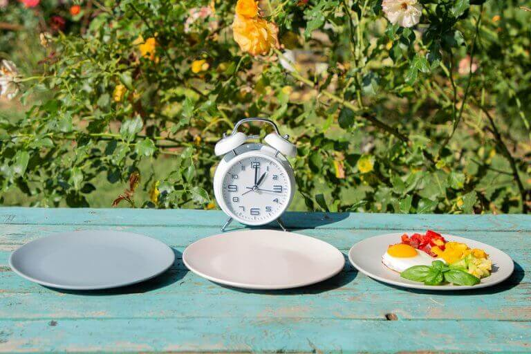 Two emply plates next to a full plate and in front of a clock to simbolize intermittent fasting