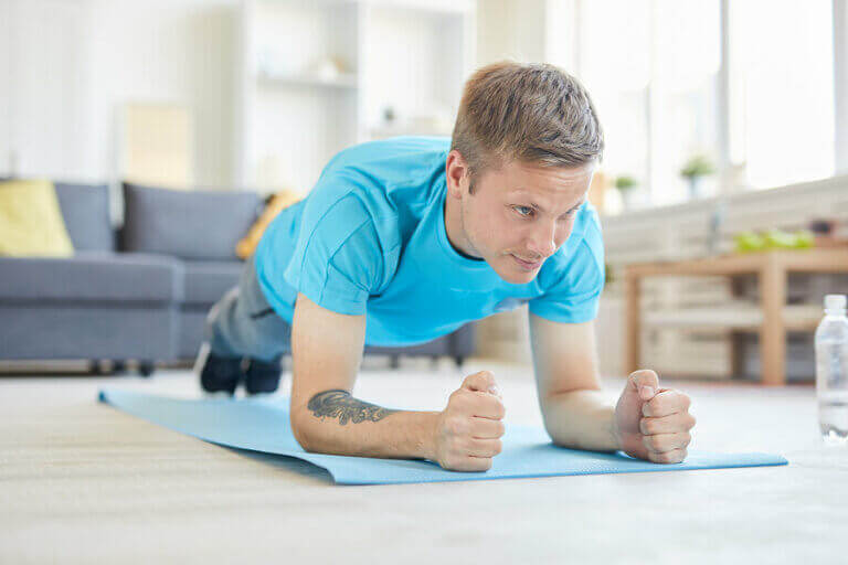 A man working out at home with one of the #yomemuevoencasa routines