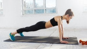 A woman performing push-ups on a yoga mat.