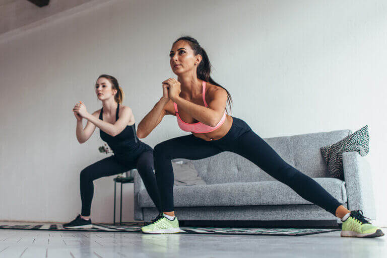 Two women doing side lunges at home during the coronavirus quarantine