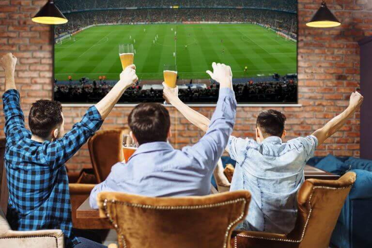 A group of three men watchin a sports event on TV