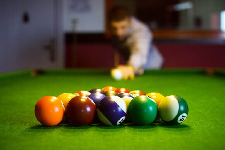 A billiard player following the competition rules during his lag shot