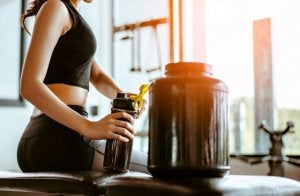 A woman at a gym drinking a supplement shake.