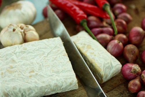 A knife cutting a slice of tempeh.