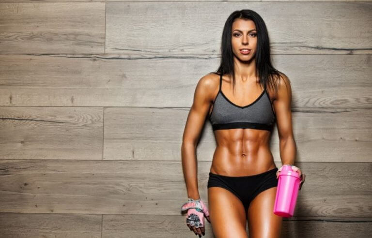 A woman drinking her arginine supplements to achieve her toned body