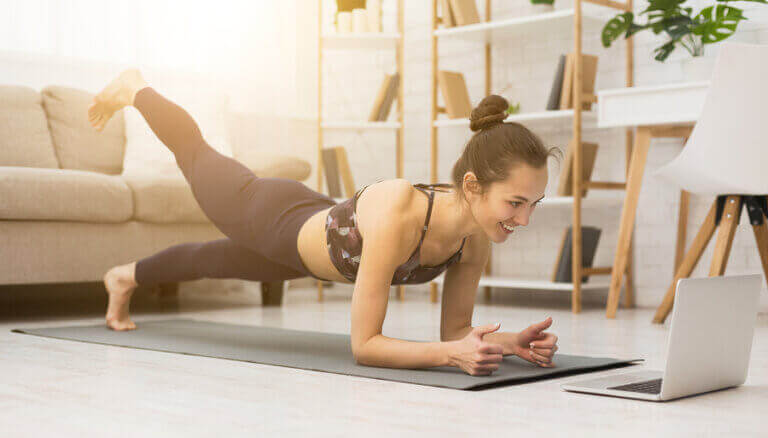 A woman working out at home while following videos from different fitness channels