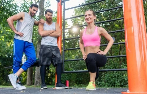 Two guys watching a woman do a lunge.