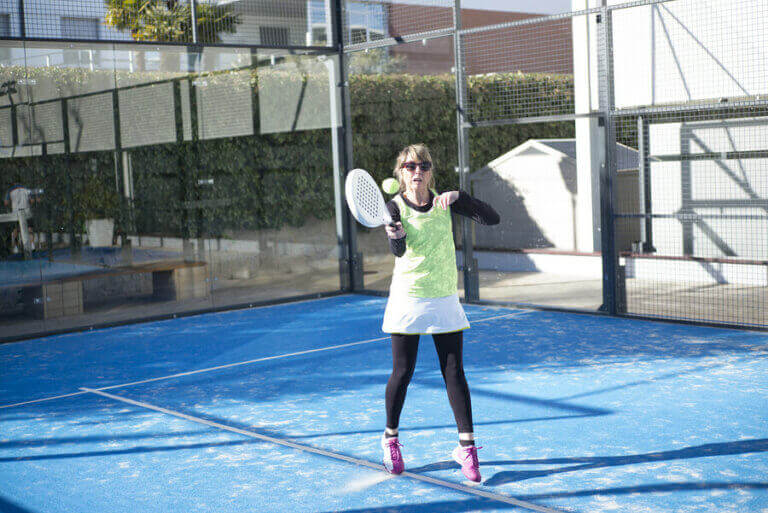 An older woman playing tennis after a transplant