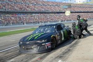 A pit crew assisting a car.