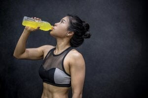 A woman drinking an energy drink.