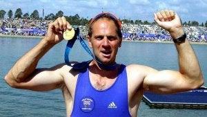 Steve Redgrave holding an Olympic gold medal.