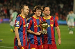 Three Barcelona soccer players on the field.