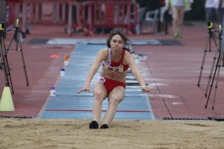 An athlete that is part of the Spanish Athletics Federation performing a long distance jump during an official competition