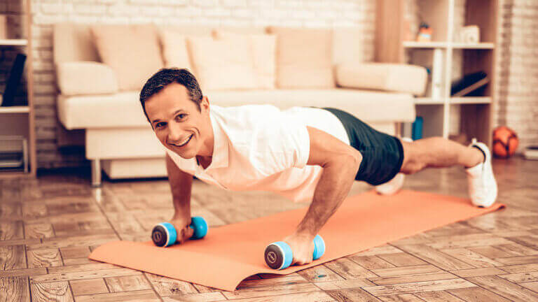 A smiling man doing dumbbell pushups at home