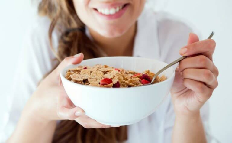 Woman eating a bowl of cereal rich in fiber to compensate for the lack of this substance in the low carb diet