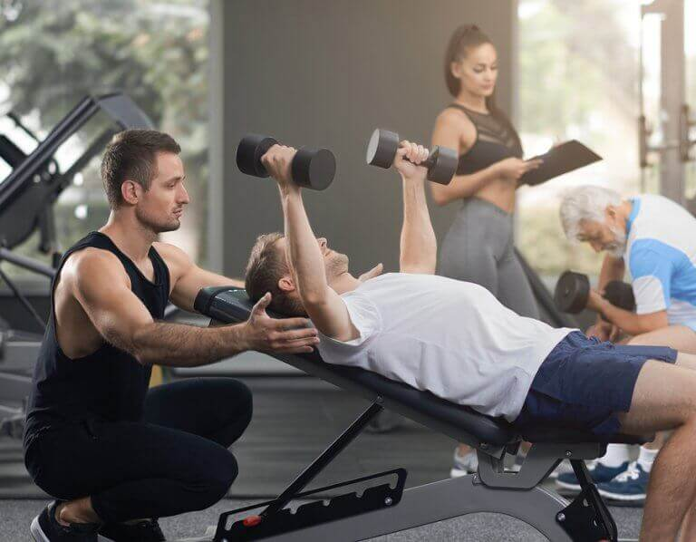 A man training with weights at the gym to increase his calorie expenditure