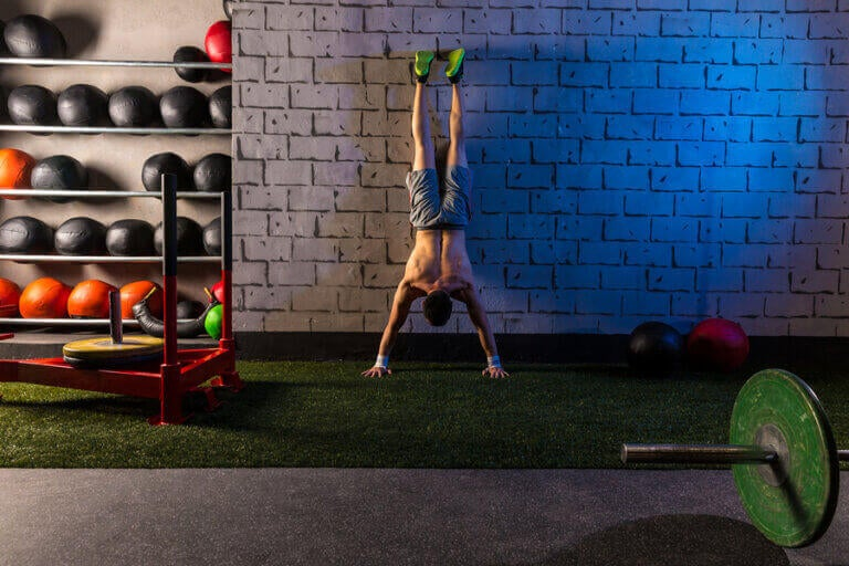 A man doing a handstand push up against the wall