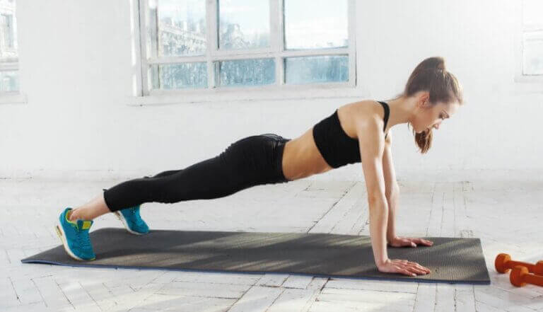 A woman doing easy CrossFit exercises like push ups to work out in her home