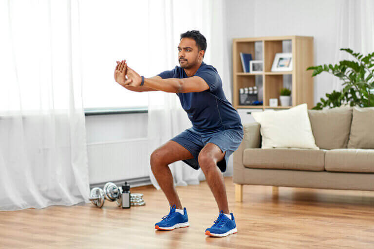 A man doing easy CrossFit exercises such as squats in the middle of his living room
