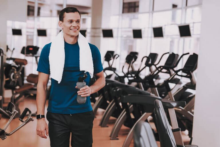 A happy gym member walking next to the elyptical machines